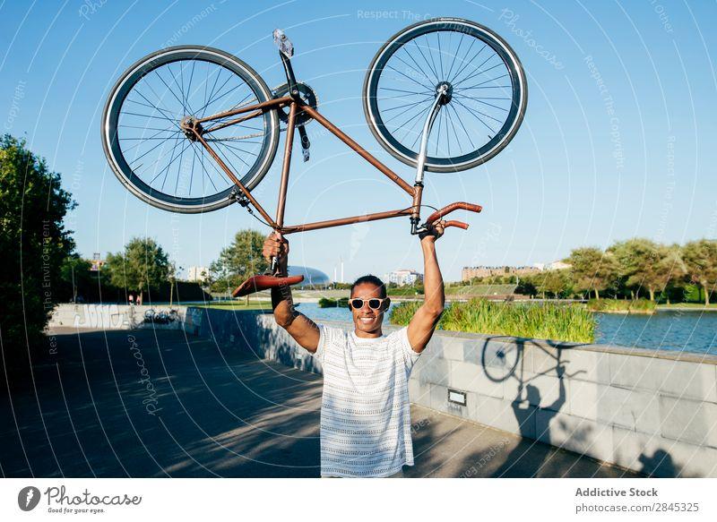 Fröhlicher Mann mit Fahrrad Halt heiter über Kopf Jugendliche schwarz lässig stehen Großstadt Mensch Lifestyle sportlich Sport Fahrradfahren Körperhaltung Glück