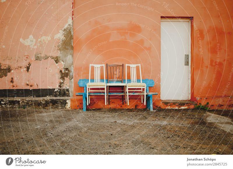 Drei Stühle auf einer Bank, Puerto de la Cruz, Teneriffa blau Farbe weiß Wand lustig Textfreiraum orange Fassade paarweise Tür Freundlichkeit Stuhl Spanien