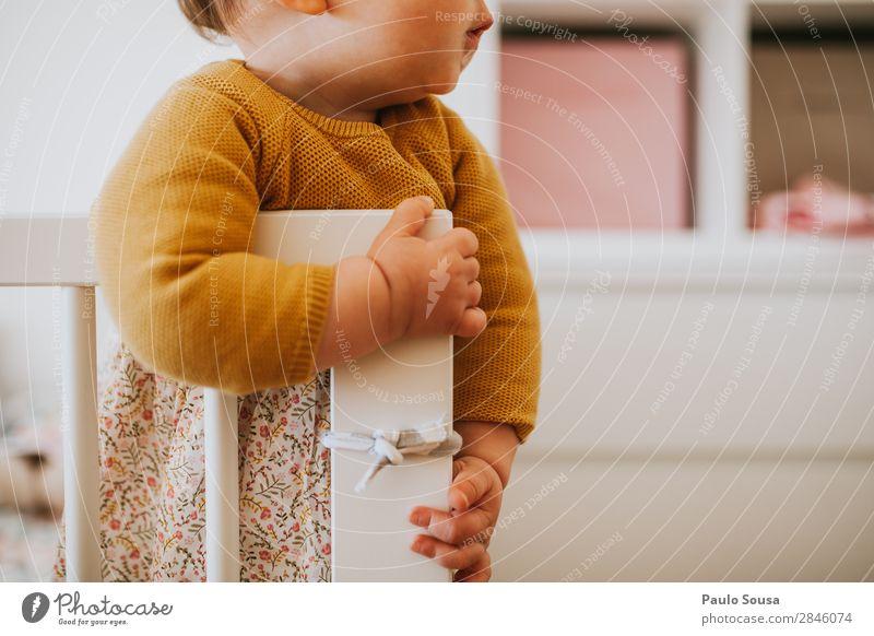 Kind steht in einer Krippe. Lifestyle einrichten Babybett Mensch feminin Kleinkind Mädchen 1 1-3 Jahre beobachten hören liegen stehen authentisch einfach