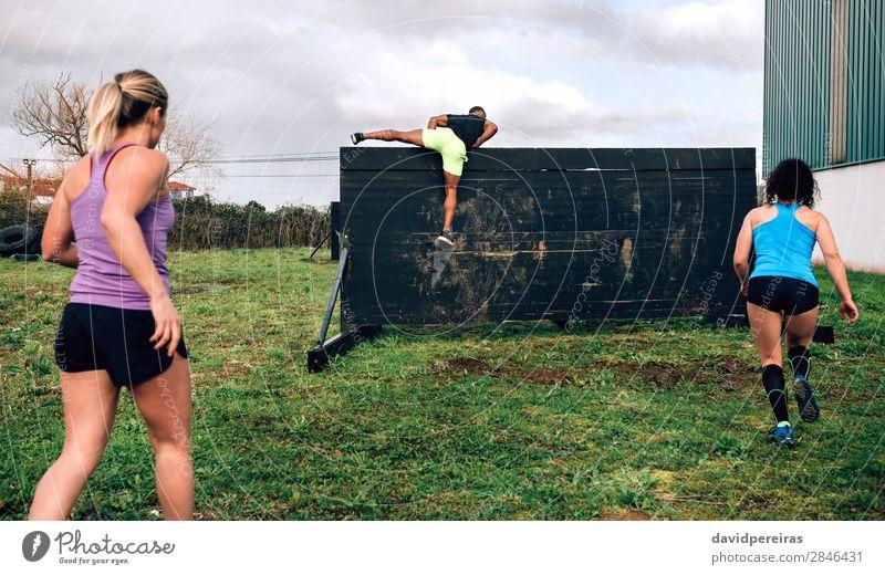 Teilnehmer des Hindernisparcours Kletterwand Lifestyle Sport Klettern Bergsteigen Mensch Frau Erwachsene Mann Menschengruppe springen authentisch stark schwarz
