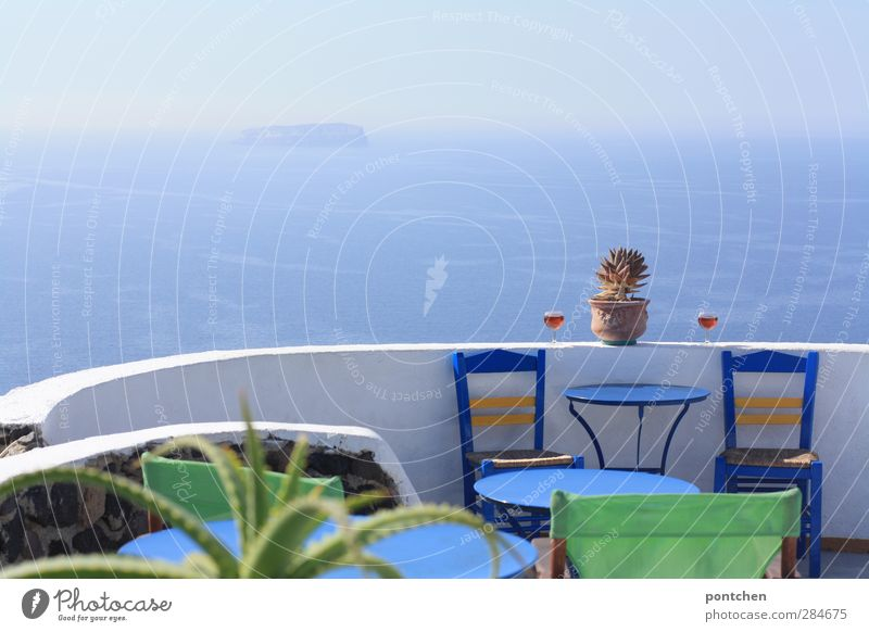 Santorini. Blick aufs Meer von einer Terrasse eines  Restaurants. Blaue stühle, Weingläser, Kaktus. Typisch griechisch Lifestyle Tourismus Bar Cocktailbar