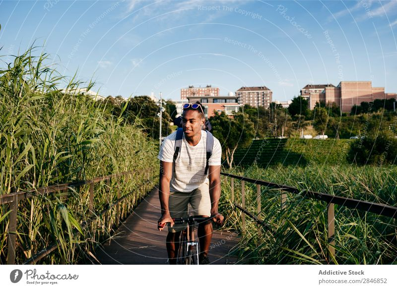 Junger Mann fährt Fahrrad auf dem Bürgersteig Straßenbelag Reiten Gras Brücke Geländer Lifestyle Verkehr Stadt Zyklus Großstadt Aktion Gasse Motorradfahren