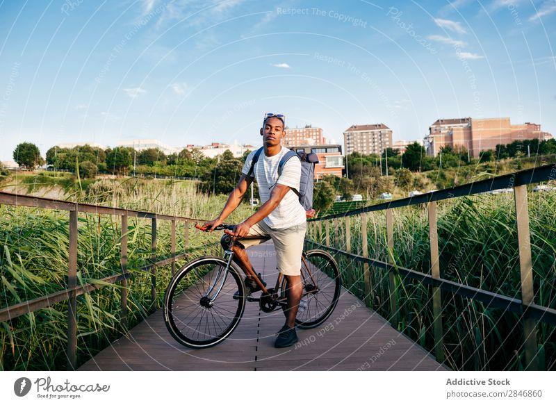Junger Mann, der mit dem Fahrrad auf dem Bürgersteig posiert. Straßenbelag Gras Brücke Geländer Lifestyle Verkehr Stadt Zyklus Großstadt Aktion Gasse