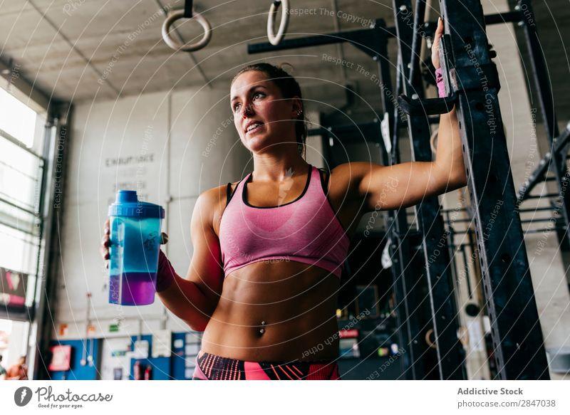 Lächelndes Mädchen beim Trinken im Fitnessstudio Frau trinken Sporthalle Erfrischung Gesundheit sportlich Körper Training Flasche Zufriedenheit heiter