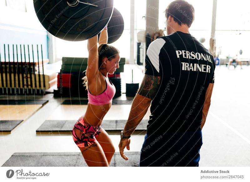 Frau mit Trainerin beim Gewichtheben Sporthalle Curl-Hantel sportlich Bodybuilder assistierend Ausbilderin Gerät Bodybuilding Gesundheit Fitness Kraft Training