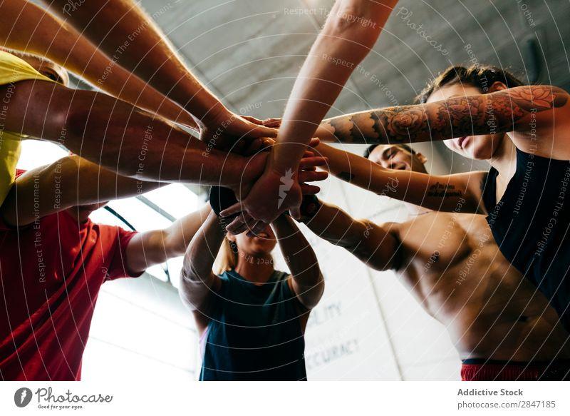 Sportliche Menschen beim Händestapeln Sportler Zusammensein Sporthalle Teamwork Hände stapeln Errungenschaft Einheit abstützen Bodybuilding heiter muskulös