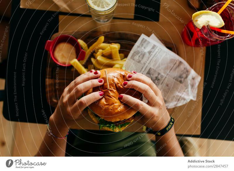 Getreidefrau beim Pflücken eines Hamburgers Burger Fries Fastfood Lebensmittel frisch Fleisch Mahlzeit ungesund Snack Belegtes Brot Geschwindigkeit Brötchen
