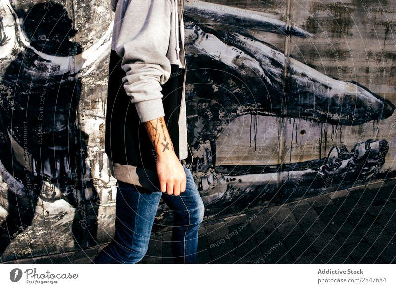 Getreide tätowierter Mann gegen die Wand mit Graffiti Stadt Schickimicki tausendjährig künstlerisch Grunge Beton Stil Großstadt selbstbewußt lässig Straße