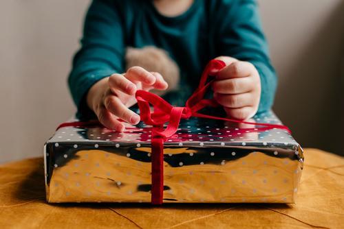 Schneiden Sie Kinder, die das Band an der Box binden. Geschenk Weihnachten & Advent Ferien & Urlaub & Reisen Kopplungsbindung Hand Schnur Kasten Glück