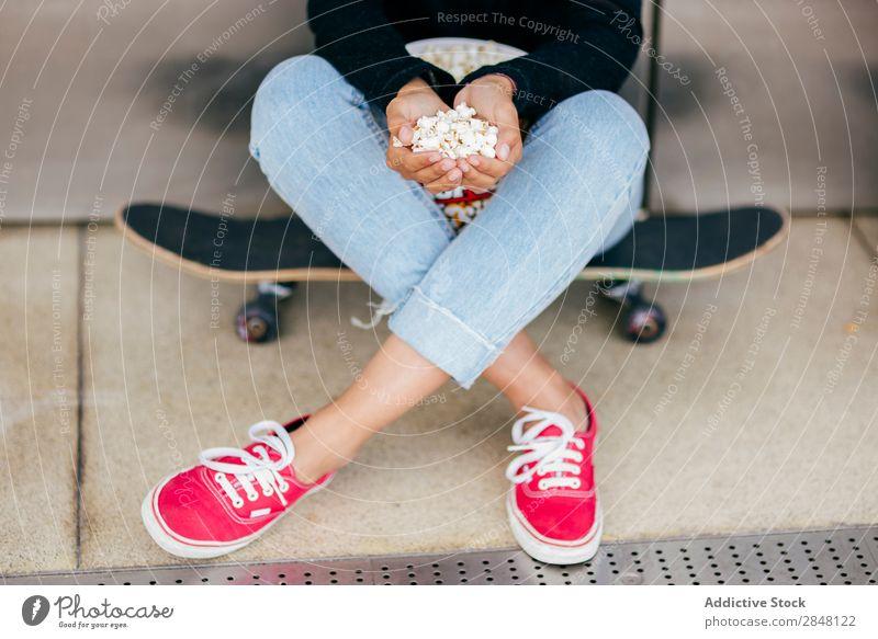 Getreide Frau mit Haufen Popcorn Popkorn Skateboard Stadt Anhäufung Jugendliche Snack Stil Halt Bekleidung Schickimicki Eimer Kultur sitzen Körperhaltung