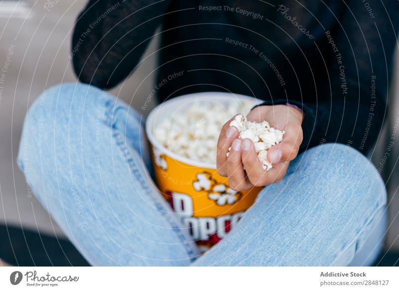 Crop Mädchen mit Popcorn in der Hand Frau Popkorn Stadt Anhäufung Jugendliche Snack Stil Halt Bekleidung Schickimicki sitzen Eimer Kultur Selbstständigkeit