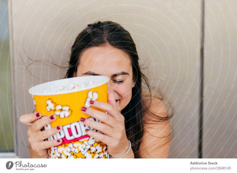 Hübsches Mädchen, das mit Popcorn posiert. Frau Youngster Popkorn lachen Freude Stadt heiter Eimer spielerisch Schickimicki Stil Bekleidung Porträt Deckfläche