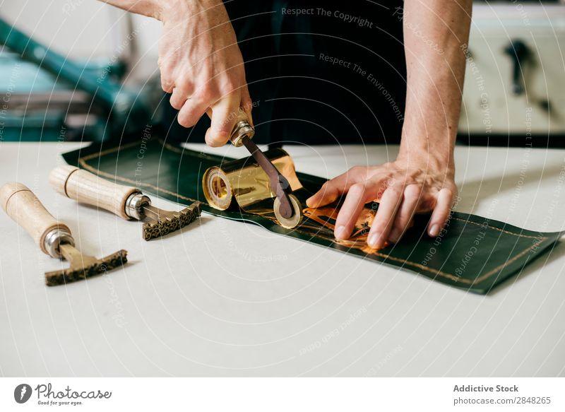 Kunsthandwerklich dekoriertes Lederstück prägen Abdruck Werkstatt Gold Stanzen Beruf Basteln verarbeiten außergewöhnlich geprägt Material Werkzeuge Instrumente
