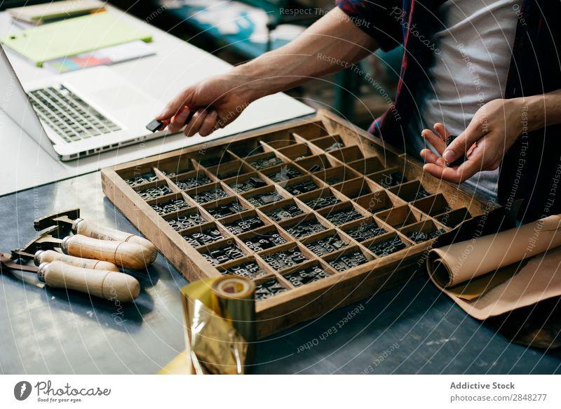Zuschneider beim Auswählen von Druckbuchstaben Kunsthandwerker Typographie Brief auserwählend Stempel Arbeitsplatz Sammlung Tradition Arbeitsbereich Ausdruck