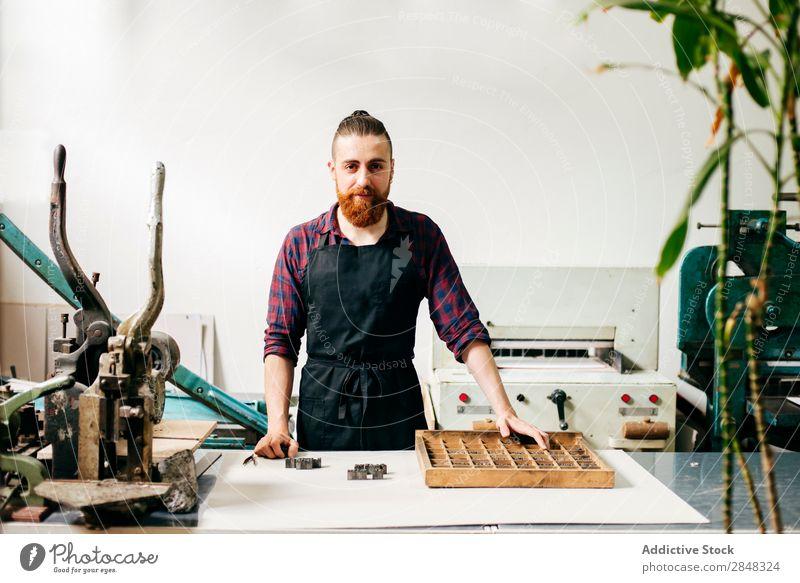 Bärtiger Mann in der Druckerei Typographie Arbeitsbereich Körperhaltung Ausdruck Buchmacherei Techniker selbstbewußt Handarbeit Brief Buchdruck Handwerkskunst