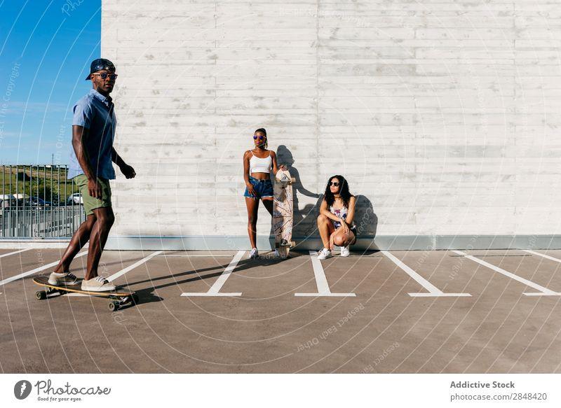Sportliche Menschen mit Skateboards auf der Straße Körperhaltung Skateboarding Sommer Reiten Selbstständigkeit Menschengruppe in Bewegung sportlich Stil