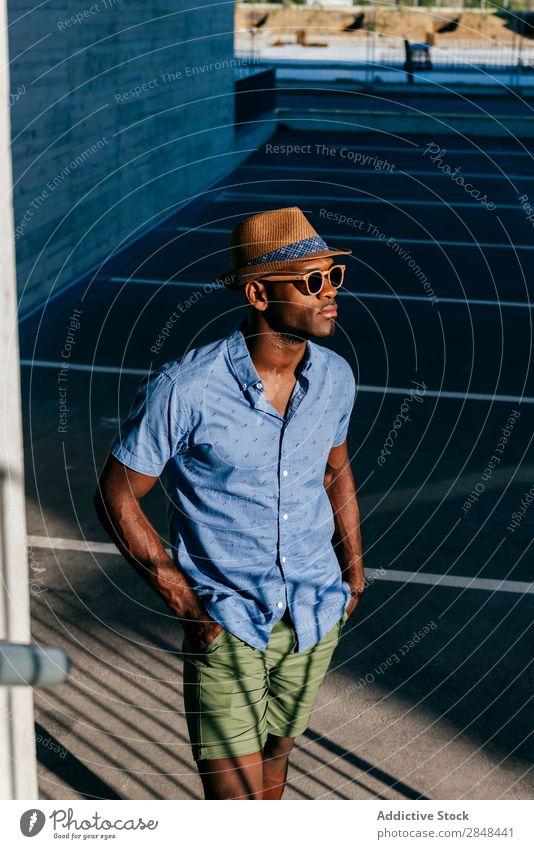 Stilvoller schwarzer Mann, der auf der Straße posiert. Sommer Körperhaltung trendy Stadt Schickimicki Hemd Bekleidung modisch gutaussehend maskulin lässig Hut