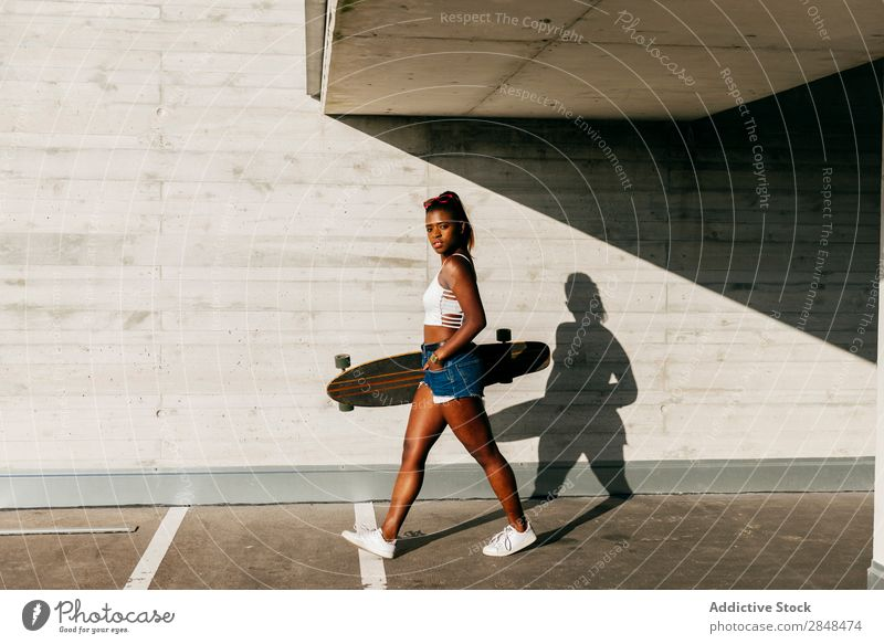 Stilvolle Frau mit Brett, die auf der Straße spazieren geht. Longboard Stadt Sport Freizeit & Hobby Skateboarderin schwarz Skateboarding Jugendliche Afrikanisch