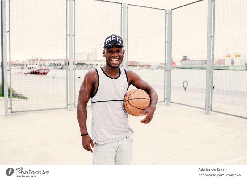 Schwarzer Mann mit Basketball Ball ausdehnend Straßenball selbstbewußt Sportpark Stadt maskulin Sportler Stil Körperhaltung Afroamerikaner Freizeit & Hobby