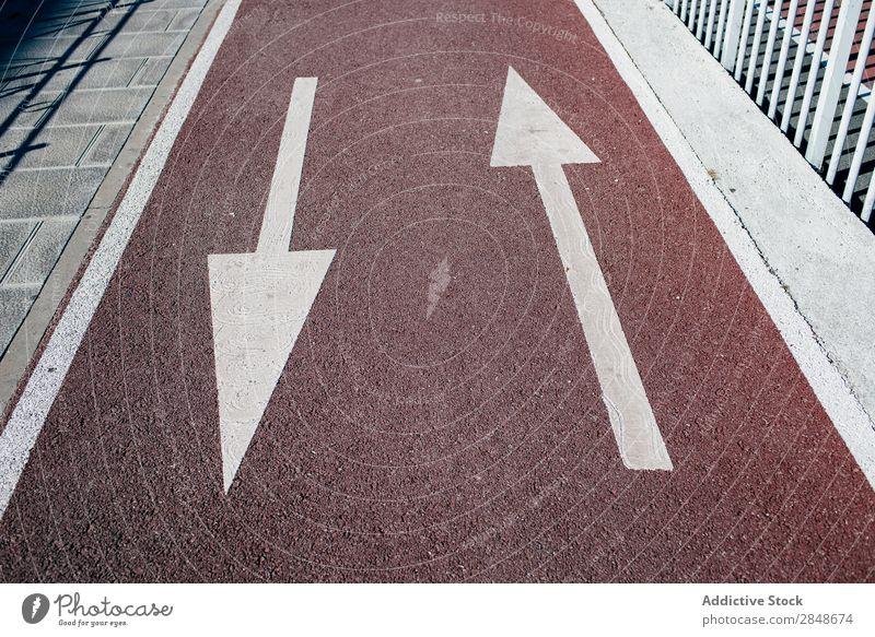 Pfeile auf dem Bürgersteig, die eine Wegbeschreibung zeigen. Straßenbelag Richtung bemalt Gummi Asphalt Stadt Konsistenz Information Anleitung