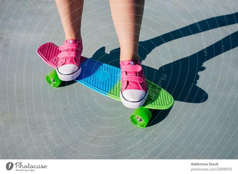 Crop Girl auf buntem Skateboard Frau mehrfarbig Longboard Bürgersteig Stil Sommer Turnschuh rosa lässig Youngster trendy Jugendliche Straße Stadt Beine modern
