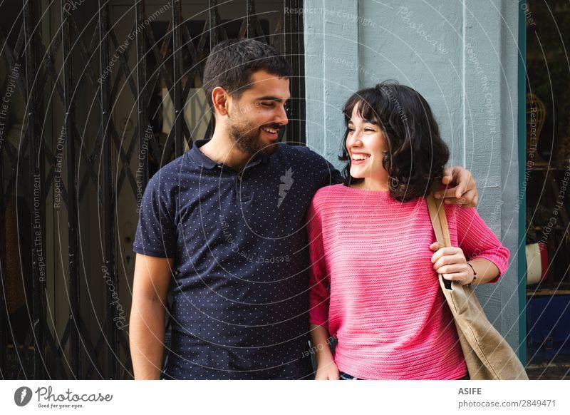 Glückliches junges Paar, das sich anlächelt. Lifestyle kaufen Freude schön Sommer Frau Erwachsene Mann Freundschaft Straße T-Shirt Pullover brünett Vollbart
