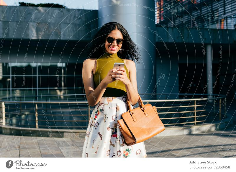 Lächelnde Frau mit Smartphone in der Stadt PDA Großstadt elegant Texten benutzend Browsen laufen Mitteilung Jugendliche Lifestyle schön Mädchen Mobile lässig