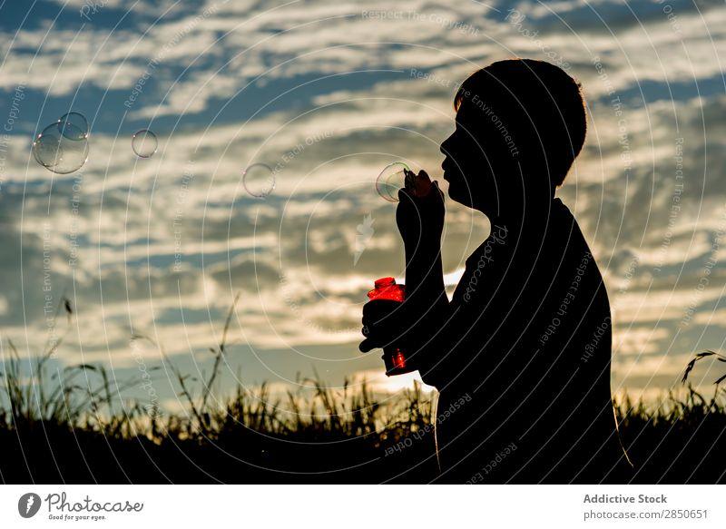 Silhouette des Jungen, der Seifenblasen bläst. Natur wehen Ferien & Urlaub & Reisen Freude Wiese hell Unbekümmertheit Entertainment Freiheit Ausdruck