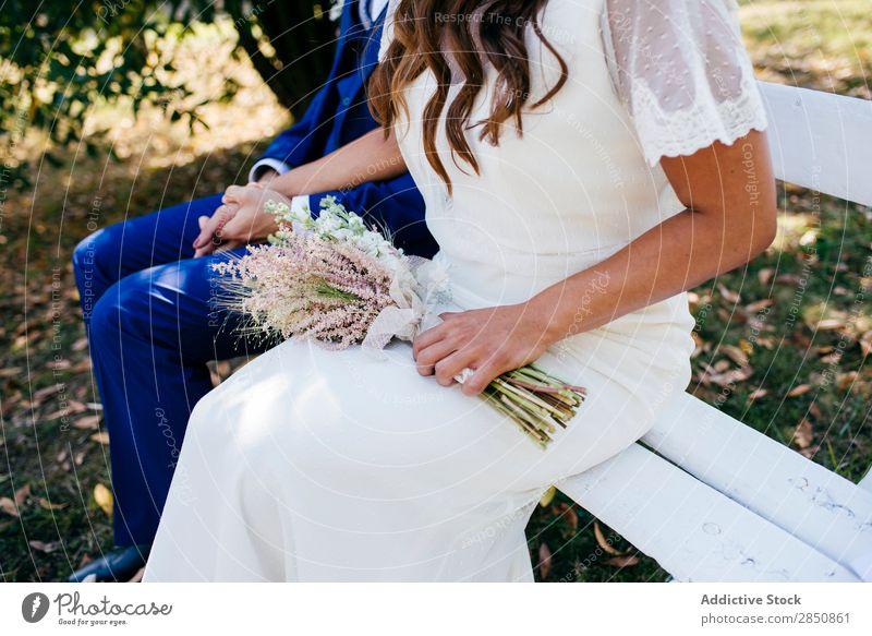 Schneiden Sie Braut und Bräutigam auf der Bank. striegeln Paar romantisch Feste & Feiern Zusammensein Händchenhalten Sommer Blume Außenaufnahme Engagement Liebe
