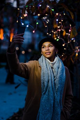 Frau, die Selfie in der Nähe eines Baumes mit Lichtern nimmt. schön Jugendliche Porträt Mensch PDA lässig Mobile Lächeln hübsch Freizeit & Hobby Handy