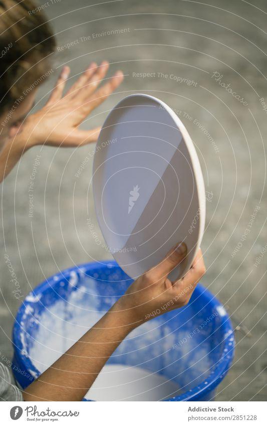 Getreideperson, die mit flüssigem Ton arbeitet. Mensch Geschirr Werkstatt liquide Keramik Handwerk selbstgemacht Handarbeit eintauchend Eimer Kunsthandwerker