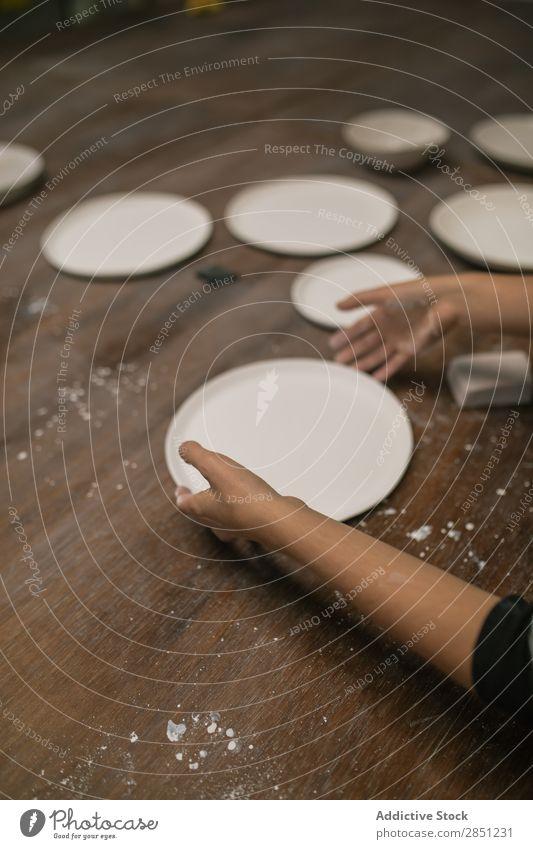 Getreideperson, die mit der Keramikplatte arbeitet. Mensch Werkstatt Teller Geschirr Handarbeit Schreibtisch machen Ton Utensil Kunst Emaille Kreativität