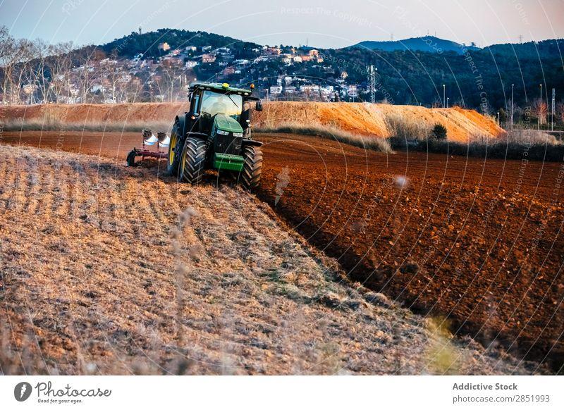 Traktor beim Pflügen des Feldes pflügen Erde Bauernhof Landschaft Ackerbau landwirtschaftlich Landen Pflug Landwirtschaft Bodenbearbeitung Gerät braun Maschine
