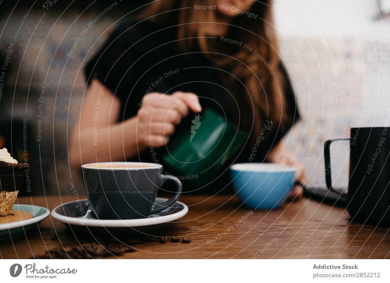 Person, die Milch in den Kaffee gießt Mensch Gießen machen Barkeeper Latte Tasse Dessert braun trinken Cappuccino heiß süß Café Lebensmittel Mokka Koffein