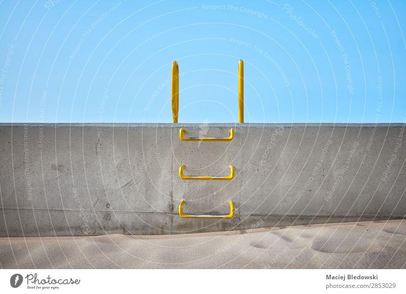 Stahlleiter, die in eine Betonwand eingebettet ist. Sand Himmel Metall blau Tapferkeit selbstbewußt Erfolg Kraft Willensstärke Mut Sicherheit Neugier Hoffnung