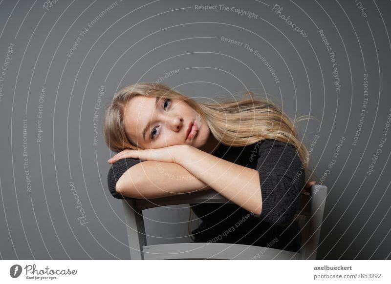 Langeweile Mensch feminin Junge Frau Jugendliche Erwachsene 1 13-18 Jahre 18-30 Jahre blond langhaarig sitzen Stuhl rittlings verkehrt Stuhllehne Traurigkeit