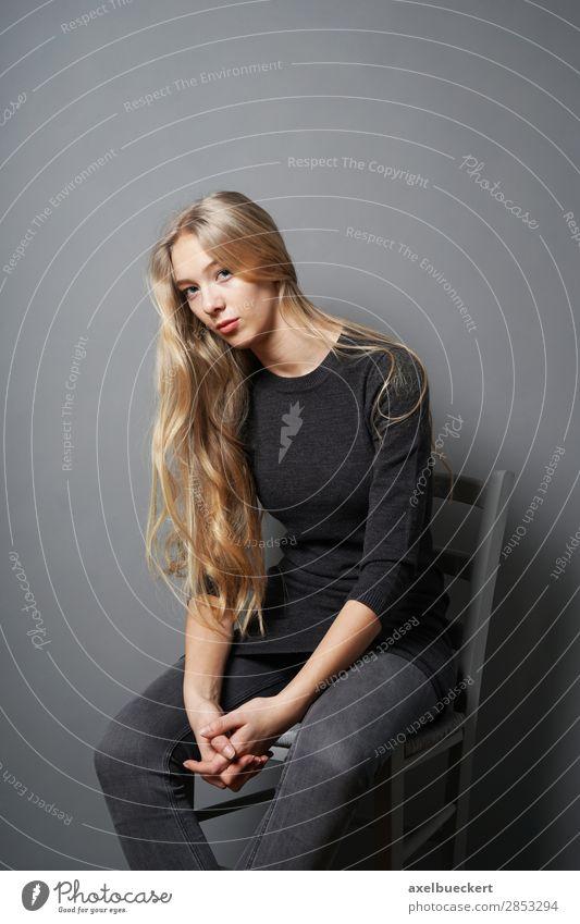 lässige junge Blondine sitzt auf Stuhl Mensch feminin Junge Frau Jugendliche Erwachsene 1 13-18 Jahre 18-30 Jahre Jeanshose blond langhaarig sitzen grau