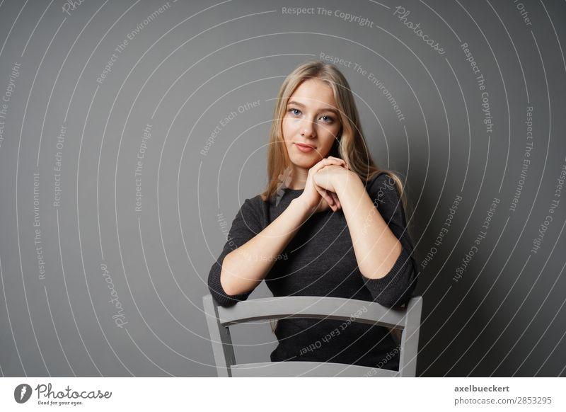 junge Frau sitzt rittlings auf Stuhl Mensch feminin Junge Frau Jugendliche Erwachsene 1 13-18 Jahre 18-30 Jahre blond langhaarig sitzen schön grau Farbfoto