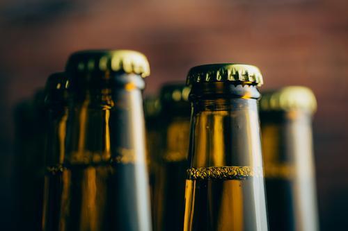 Gruppe von Bierflaschen schießen mit selektivem Fokus Alkohol Getränk Unschärfe Flasche Brauerei Backstein kalt Coolness Handwerk dunkel trinken Schaum