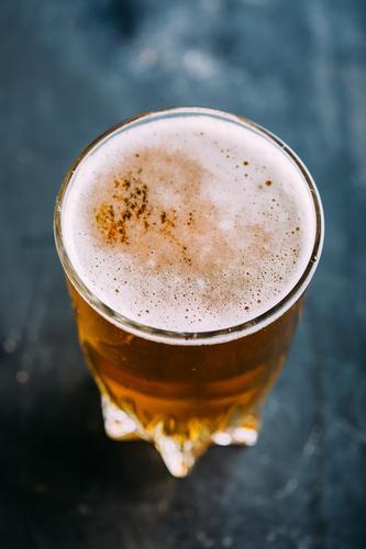 Glas Bier auf dunklem Hintergrund Alkohol Bar Getränk Flasche Brauerei Coolness Handwerk trinken Schaum Lebensmittel gold Grunge Pub Tisch durstig Holz