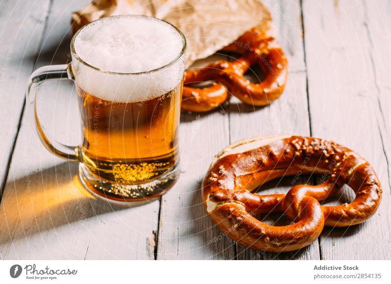 Bierglas und Brezel Bar Getränk Coolness trinken Schaum Lebensmittel Glas gold Becher Oktoberfest rustikal Salz Snack Tisch durstig altehrwürdig Holz