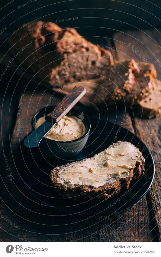 Rustikales Brot mit Butter backen Bäckerei Kohlenhydrat dunkel Mehl Lebensmittel frisch selbstgebacken Brotlaib Stimmung rustikal Aufstrich Weizen Holz