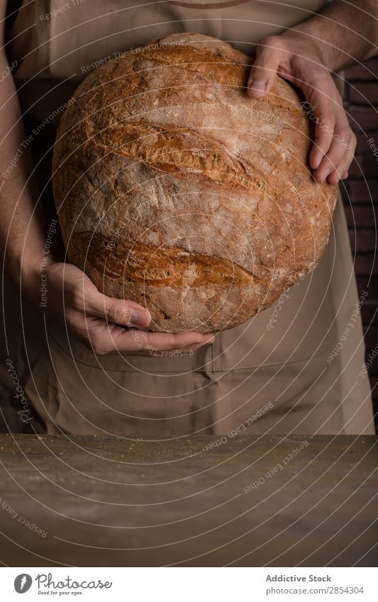 Ein Mann hält einen frisch gebackenen Brotlaib. Bäckerei Frühstück Kohlenhydrat geschnitten dunkel Mehl Lebensmittel Hand selbstgemacht selbstgebacken gebastelt