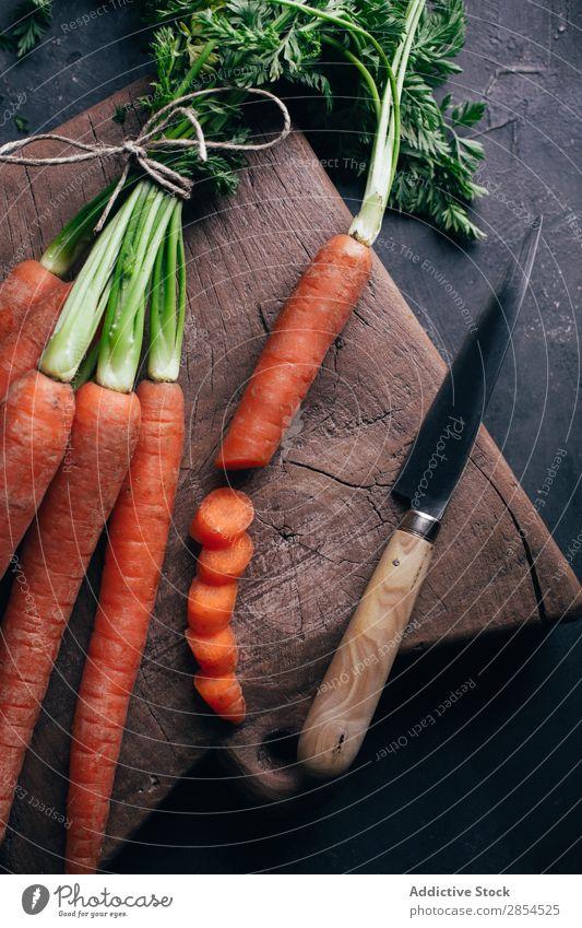 Frische Karotten in einem Holzschneidebrett Hintergrundbild Bündel Möhre mehrfarbig dunkel Lebensmittel frisch Ernte Gesundheit Messer Metall Ernährung Orange
