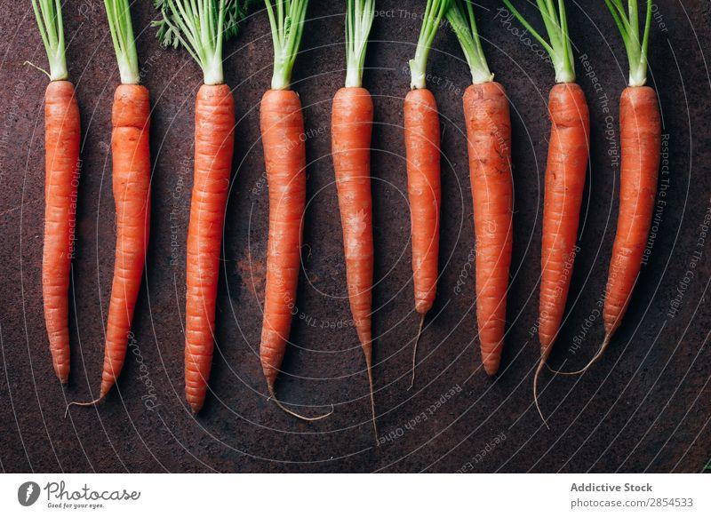 Ein Haufen frischer Karotten in dunklem metallischem Hintergrund. Hintergrundbild Möhre mehrfarbig dunkel Lebensmittel Ernte Gesundheit Metall Ernährung Orange