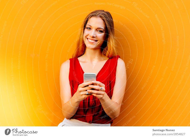 Porträt einer schönen jungen Frau mit Handy auf der Straße. Telefon Glück Mobile Jugendliche Wand Texten Tippen PDA benutzend Lächeln Dame attraktiv