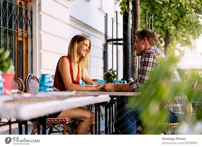 Junges Paar, das Spaß in der Stadt hat. sitzen Partnerschaft Liebe Jugendliche Halt Hand Blick Glück lachen Restaurant Terrasse Lächeln Mensch Liebespaar