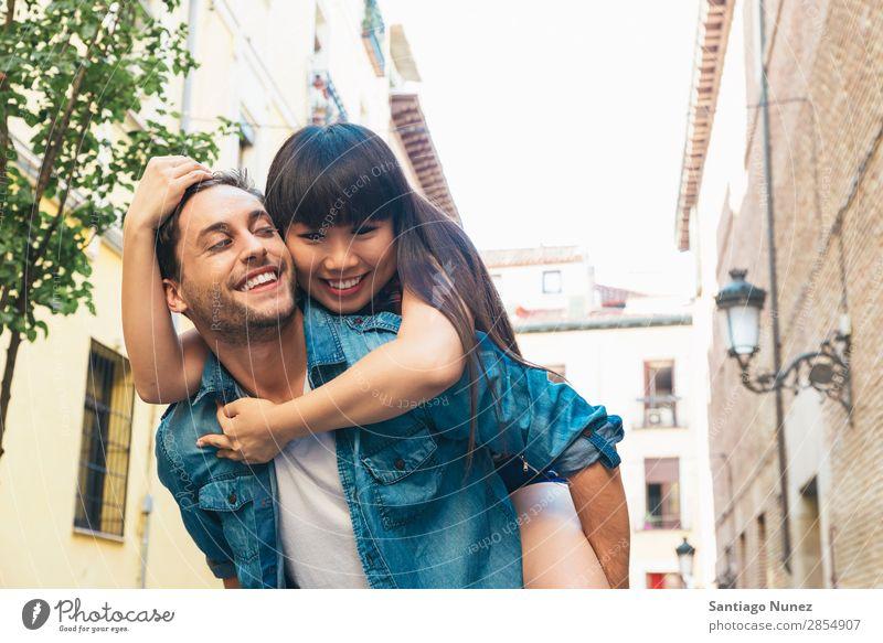 Ein glückliches, liebevolles Paar. Ein glücklicher junger Mann huckepack, der seine Freundin unterstützt. asiatisch schön Unbekümmertheit heiter Chinese