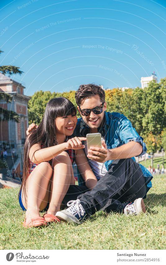 Junges glückliches Paar mit Smartphones im Park asiatisch schön Freund lässig Solarzelle Handy Chinese Mitteilung Verbindung Textfreiraum Europa Frau