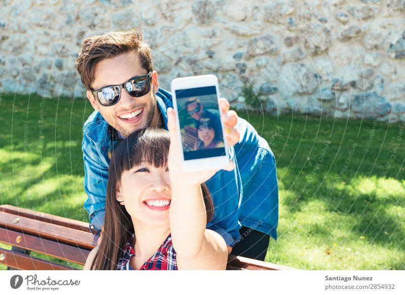 Junges glückliches Paar mit Smartphone im Park schön lässig Solarzelle Handy Chinese Mitteilung Verbindung Textfreiraum